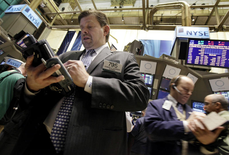 FILE - In this Jan. 25, 2011 file photo, trader Edward Schreier, left, works on the floor of the New York Stock Exchange. (AP Photo/Richard Drew, file)