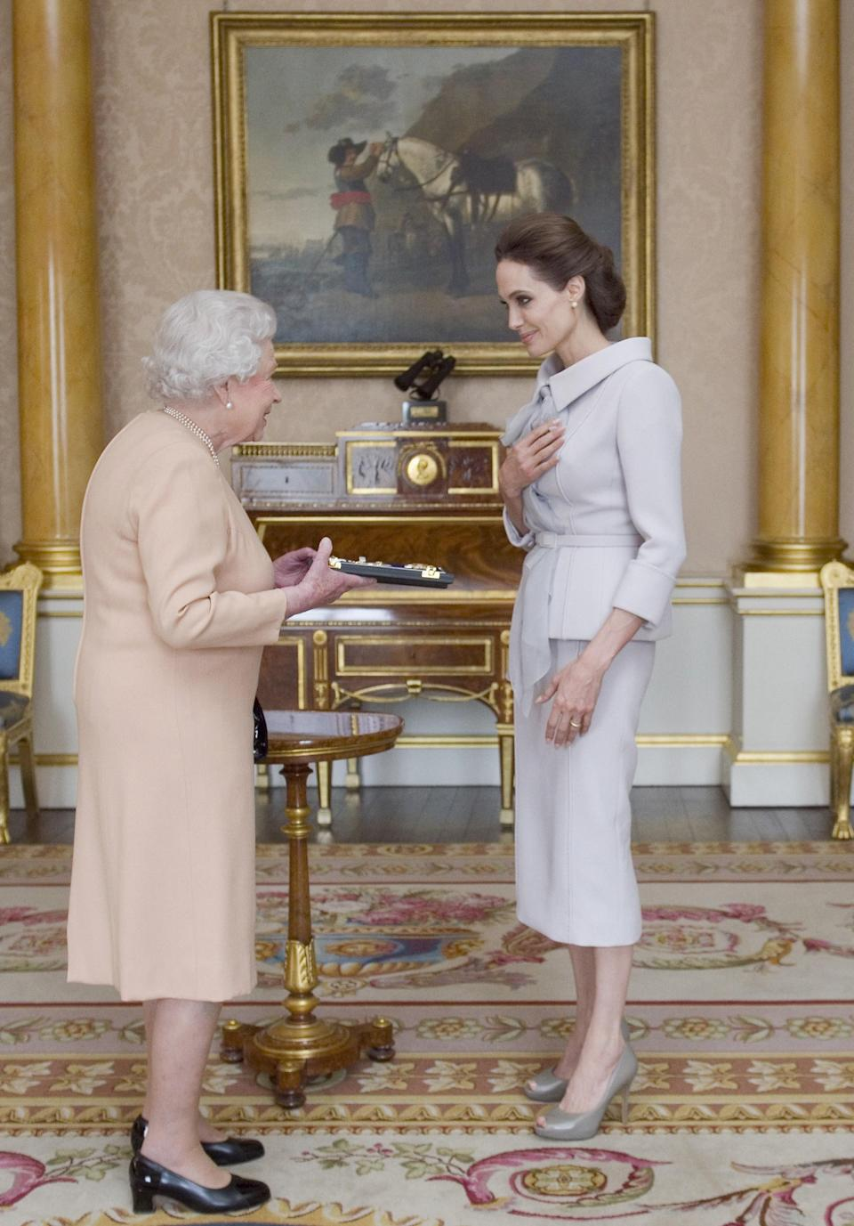 <p>Back in 2014, Angelina Jolie was made an honorary dame by the Queen for her campaign work against sexual violence. For the occasion, she chose a chic Ralph and Russo skirt suit Meghan Markle would approve of finished with matching Salvatore Ferragamo shoes. <em>[Photo: Getty]</em> </p>