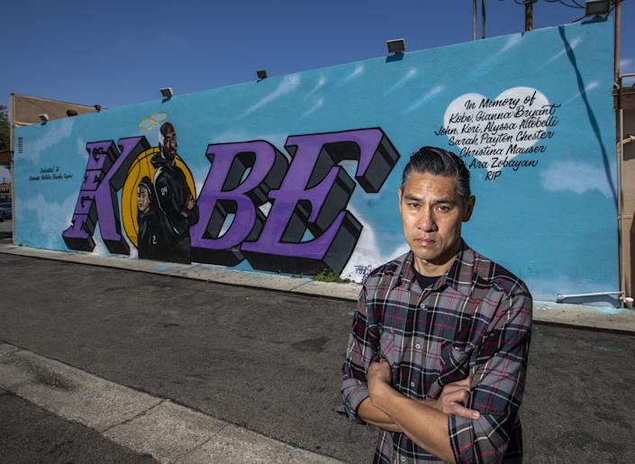 "Graffiti artist Tyke Witnes stands in front of his Kobe tribute mural at El Toro Bravo Tortilleria in Costa Mesa, which he painted three days after Kobe Bryant, his daughter Gianna and seven others were killed in a helicopter crash on Jan. 26. <span class=""copyright"">(Allen J. Schaben / Los Angeles Times)</span>"