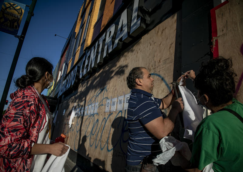 FILE - In this Saturday, May 30, 2020 file photo, business owners from Mercado Central, a cooperative of largely Latino-owned businesses on Lake Street, nail pieces of white cloth onto the boarded-up building as a symbol of peace and a possible deterrent against rioting, in Minneapolis. The destruction caused by vandals and looters, who struck as demonstrators took to the streets in reaction to the killing of George Floyd, has devastated small businesses already reeling from the coronavirus outbreak. (AP Photo/Bebeto Matthews)