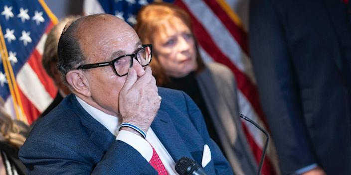 Rudy Giuliani covers his mouth with his hand at a press conference, with American flags visible in the background.
