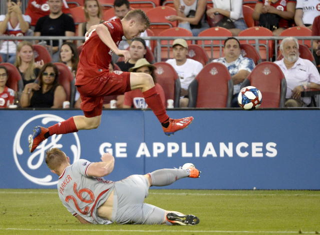 Toronto FC midfielder Jacob Shaffelburg (24) leaps over New York Red Bulls defender Tim Parker (26) during the first half of an MLS soccer match Wednesday, July 17, 2019, in Toronto. (Nathan Denette/The Canadian Press via AP)