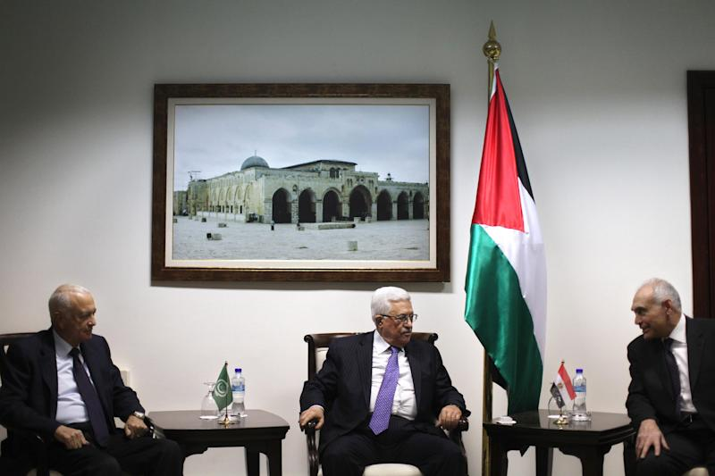 Palestinian President Mahmoud Abbas, center, sits with Arab League Secretary-General Nabil Elaraby, left, and Egyptian Foreign Minister Mohamed Kamel Amr, right, during their meeting in the West Bank city of Ramallah, Saturday, Dec. 29, 2012. (AP Photo/Fadi Arouri, Pool)