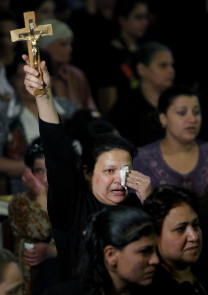 An Egyptian Christian holds a cross during a funeral service at the Saint Mark Coptic cathedral in Cairo, Egypt, Sunday, April 7, 2013. Several Egyptians including 4 Christians and a Muslim were killed in sectarian clashes before dawn in Qalubiya, just outside of Cairo on Saturday, April 6, 2013. (AP Photo/Amr Nabil)