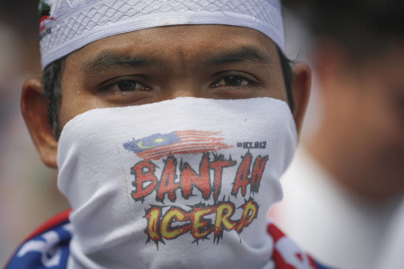 "A protester covering his face takes a part in a rally to celebrate the government's move to withdraw plans to ratify a U.N. anti-discrimination convention called ICERD, in Kuala Lumpur, Malaysia, Saturday, Dec. 8, 2018. The rally, organized by opposition Malay parties and nongovernment groups, was initially aimed at protesting a government plan to ratify a U.N. treaty against racial discrimination that critics allege will end Malay privileges under a decades-old affirmative action policy. The plan was eventually abandoned, but organizers decided to proceed with what they called a ""thanksgiving"" rally. ICERD stands for International Convention on the Elimination of All Forms of Racial Discrimination.(AP Photo/Vincent Thian)"