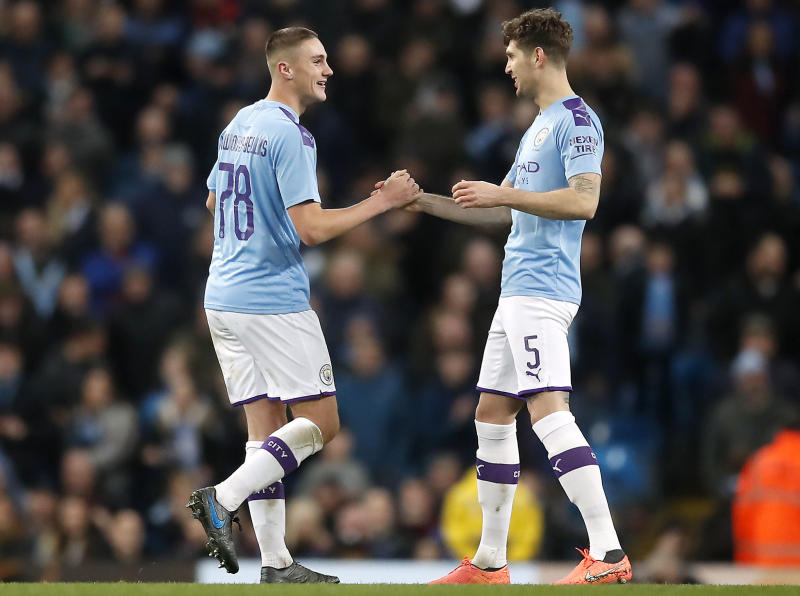 Manchester City's Taylor Harwood-Bellis, right, celebrates scoring his side's third goal of the game with teammate John Stones during the English FA Cup third round soccer match between Manchester City and Port Vale at the Etihad Stadium, Manchester, England, Saturday, Jan. 4, 2020. (Martin Rickett/PA via AP)