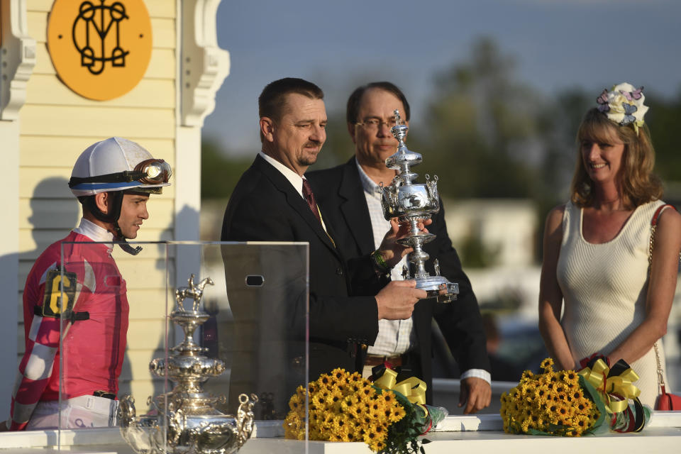 Rombauer trainer Michael McCarthy, second from left, holds the trophy as jockey Flavien Prat, left, and horse owners John Fradkin and Diane Fradkin look on after winning the 145th Preakness Stakes horse race at Pimlico Race Course, Saturday, May 15, 2021, in Baltimore. (AP Photo/Will Newton)