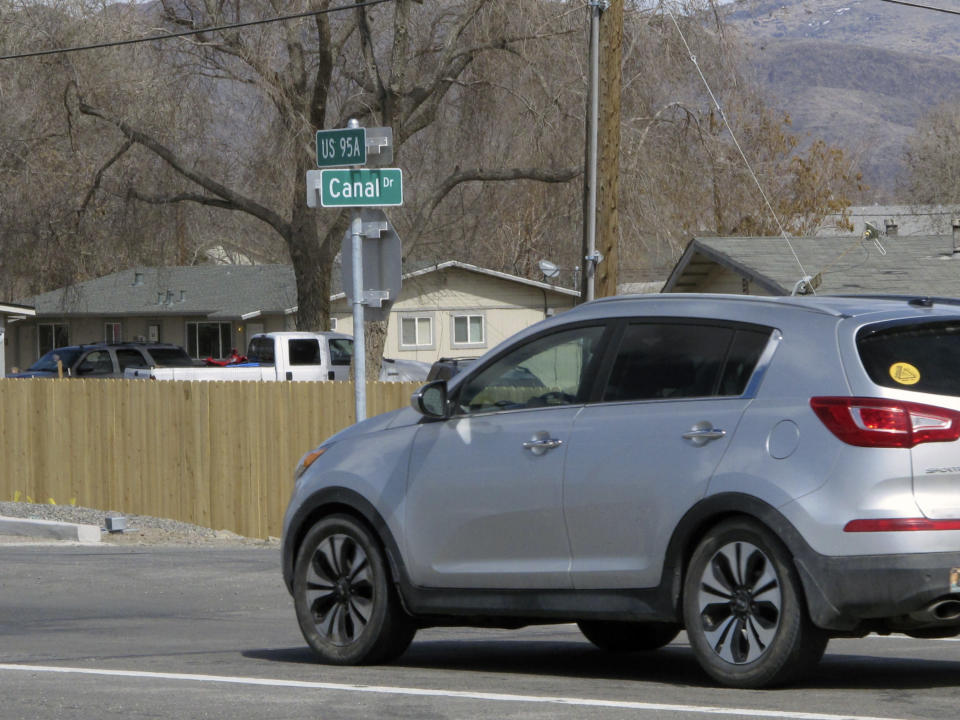 A car traveling on U.S. Highway 95 passes Canal Drive along an irrigation canal that was built in 1905, Thursday, March 18, 2021 in Fernley, Nev. The town founded by pioneers lured to the West a century ago with the promise of free land and cheap water is suing the U.S. government over plans to renovate the earthen irrigation canal that burst and flooded nearly 600 homes in Fernley in 2008. (AP Photo/Scott Sonner).