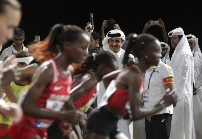 Emir of Qatar Sheikh Tamim bin Hamad Al Thani fires the starting pistol to get the women's marathon underway at the World Athletics Championships in Doha, Qatar, Saturday, Sept. 28, 2019. (AP Photo/Hassan Ammar)