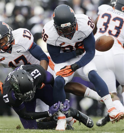 Illinois kick returner Justin Green (26) fumbles the ball as he is hit by Northwestern cornerback C.J. Bryant (13)during the first half of an NCAA college football game in Evanston, Ill., Saturday, Nov. 24, 2012. Northwestern recovered the ball. (AP Photo/Nam Y. Huh)