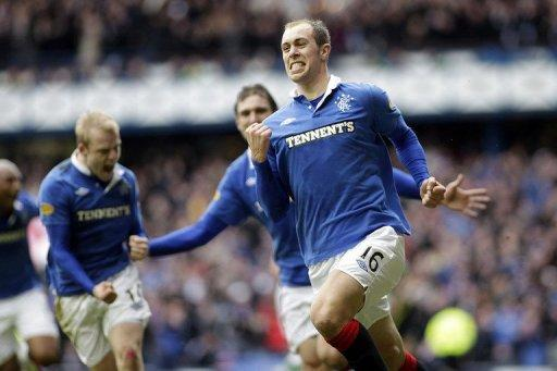 Rangers' Steven Whittaker (R) celebrates scoring during a match in February 2011. Rangers took advantage of Celtic's involvement in the Scottish Cup to move a point clear at the top of the Scottish Premier League with a narrow 2-1 win over St Mirren