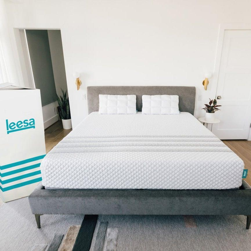"""<h3><a href=""""https://www.leesa.com/products/leesa-hybrid-mattress"""" rel=""""nofollow noopener"""" target=""""_blank"""" data-ylk=""""slk:Leesa Hybrid Mattress"""" class=""""link rapid-noclick-resp"""">Leesa Hybrid Mattress</a></h3><br><strong>Mattress Type: </strong>Hybrid (Foam & Spring)<br><strong>Sleeper Style: </strong>Hot<br><strong>Pros: </strong>Cooling Support<br><strong>Cons: </strong>Out-Of-The-Box Smell<br><br>""""My partner and I put a lot of research into finding the best mattress that would offer support and not trap heat — which was our biggest qualm with our last Tempur-Pedic foam bed. We loved how it gave us back and hip support, but hated waking up in a sweat in the middle of the night.""""<br><br>""""We were hopeful the Leesa would hold up to its claims and decided to upgrade to a King. Unfortunately, our bed frame arrived late, and the Leesa stayed in the box for two weeks. Big mistake. I didn't realize that when you leave a foam mattress in a box, it can intensify that new mattress chemical-y smell. The Leesa smelled so strong the first night, it made me nauseous. It didn't bother my partner as much. (For this reason, the company strongly urges customers to remove the mattress from the box asap.)""""<br><br>""""Thankfully, the smell dissipated quickly, because now we couldn't love our mattress more. It provides the perfect amount of support — we both live pretty active lives and never wake up sore, achy, or like we slept on something wrong, which was a common occurrence before. The foam is soft enough that it's comfortable but firm enough that one of us can move in the middle of the night and the other doesn't feel a thing. We've honestly found the best mattress for giving us <em>both</em> the best sleep ever.""""<br><br>""""As for the cooling claims, it's definitely an improvement from our last bed, but we both still run pretty hot. We ordered new cooling sheets and a comforter and if that doesn't help, we're just going to have to be one of those couples that cuddle for five minutes and th"""