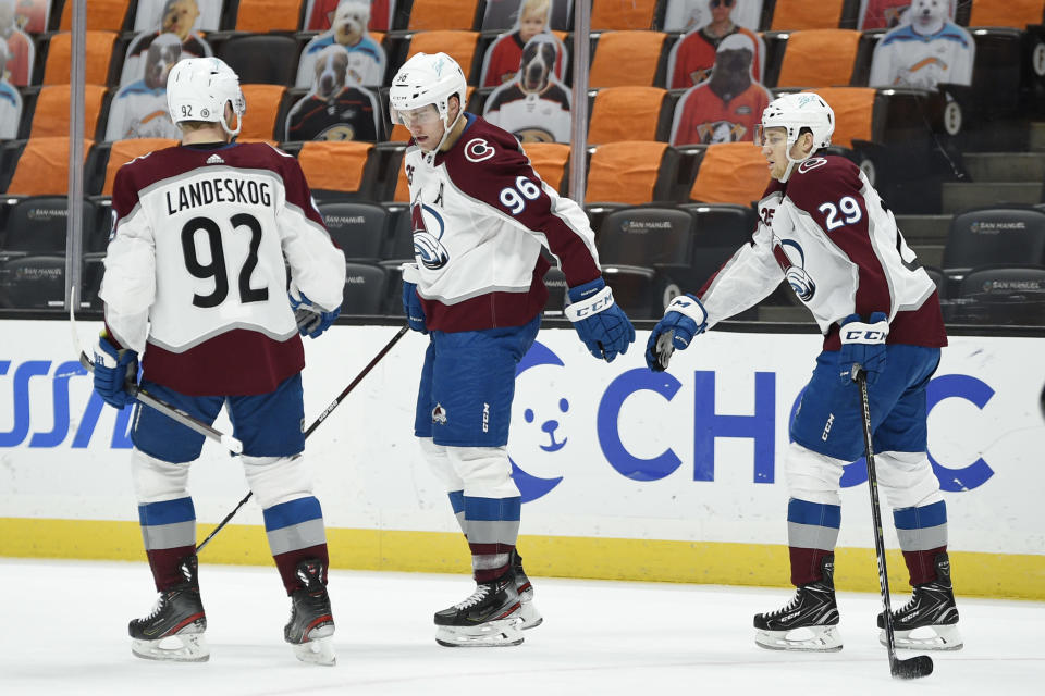 Colorado Avalanche left wing Mikko Rantanen, center, celebrates his empty-net goal with right wing Nathan MacKinnon and left wing Gabriel Landeskog, left, during the third period of the team's NHL hockey game against the Anaheim Ducks in Anaheim, Calif., Friday, April 9, 2021. The Avalanche won 2-0. (AP Photo/Kelvin Kuo)