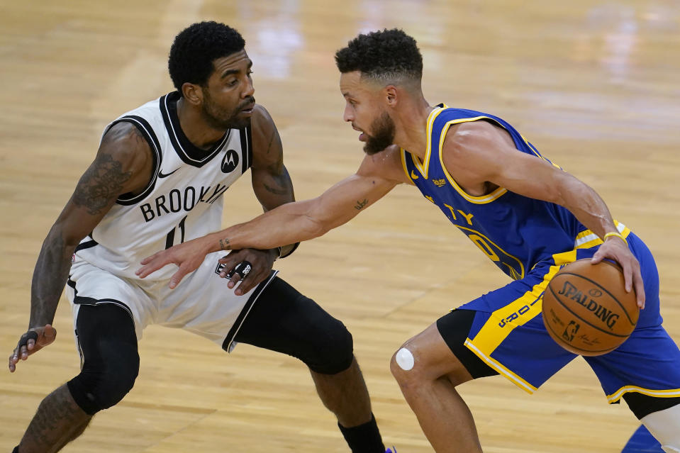 Golden State Warriors guard Stephen Curry, right, drives against Brooklyn Nets guard Kyrie Irving during the first half of an NBA basketball game in San Francisco, Saturday, Feb. 13, 2021. (AP Photo/Jeff Chiu)