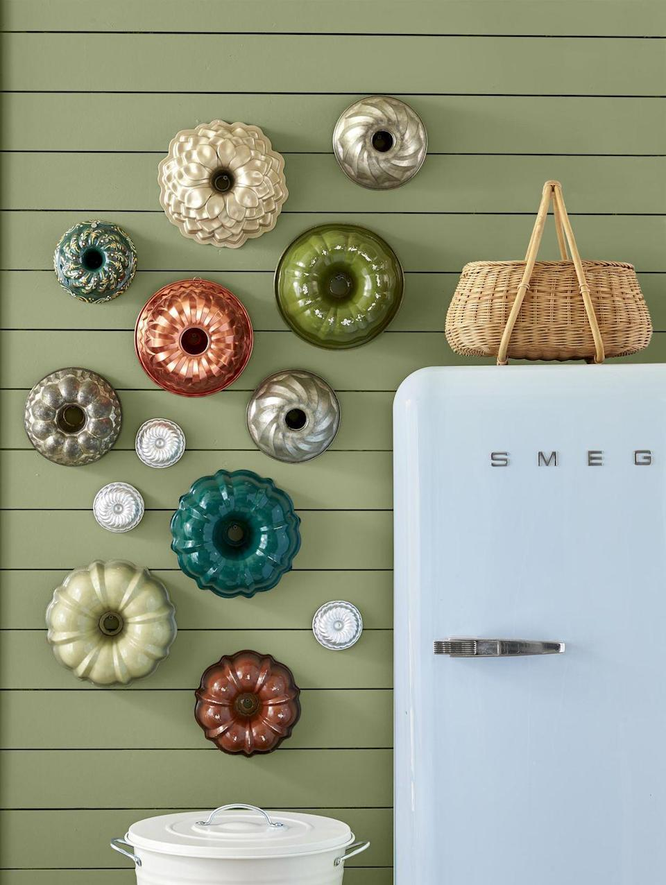 <p>A collection of colorful vintage Bundt pans in assorted shapes lends retro flair to a kitchen or pantry wall. Bonus: You can take 'em down and use them as needed. Hang using magnets or strips of double-sided velcro.</p>
