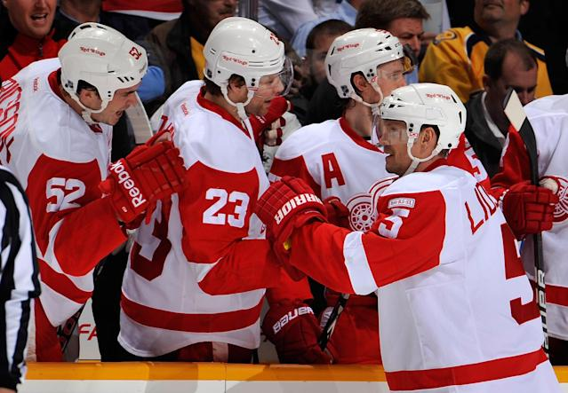 NASHVILLE, TN - DECEMBER 15: Jonathan Ericsson #53 and Brad Stuart #23 of the Detroit Red Wings congratulate teammate Nicklas Lidstrom #5 on scoring a goal against the Nashville Predators at the Bridgestone Arena on December 15, 2011 in Nashville, Tennessee. (Photo by Frederick Breedon/Getty Images)