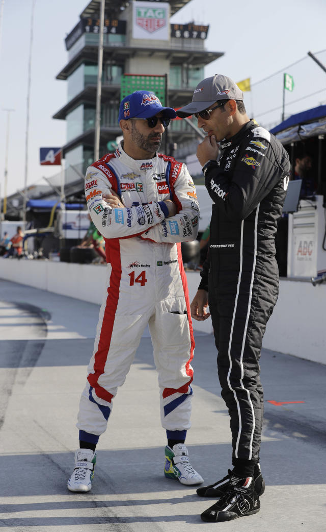 Helio Castroneves, right, of Brazil, talks with Tony Kanaan, of Brazil, before a practice session for the IndyCar Grand Prix auto race at Indianapolis Motor Speedway, in Indianapolis Friday, May 11, 2018. (AP Photo/Darron Cummings)