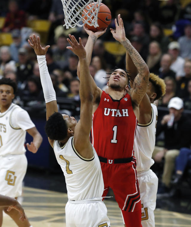 Utah forward Timmy Allen, center, goes up for a basket between Colorado guards D'Shawn Schwartz, back, and Tyler Bey in the first half of an NCAA college basketball game Sunday, Jan. 12, 2020, in Boulder, Colo. (AP Photo/David Zalubowski)