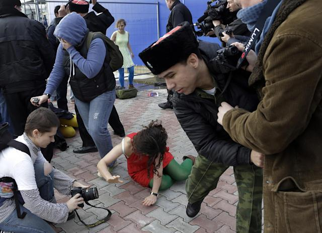 A member of the punk group Pussy Riot lies on the ground as the group are attacked by Cossack militia in Sochi, Russia, on Wednesday, Feb. 19, 2014. The group had gathered to perform in a downtown Sochi restaurant, about 30km (21miles) from where the Winter Olympics are being held.They left the restaurant wearing bright dresses and ski masks and had only been performing for a few seconds when they were set upon by Cossacks