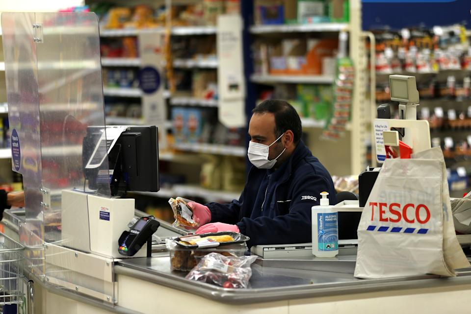 A Tesco supermarket cashier wearing protective face mask and gloves assists a shopper behind a plastic screen in a supermarket in north London as the coronavirus pandemic continues to grow in the UK