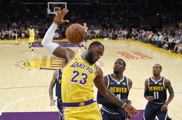 FILE - In this Tuesday, Oct. 2, 2018, file photo, Los Angeles Lakers forward LeBron James, left, dunks as Denver Nuggets forward Paul Millsap, center, and guard Monte Morris watch during the first half of an NBA basketball game in Los Angeles. James says he didn't choose the Lakers as his free-agent destination because of his burgeoning career as a Hollywood producer and performer. He remains focused on basketball, and he wants to create a winning team to end the Lakers' franchise-record five years without a playoff berth. (AP Photo/Mark J. Terrill, File)