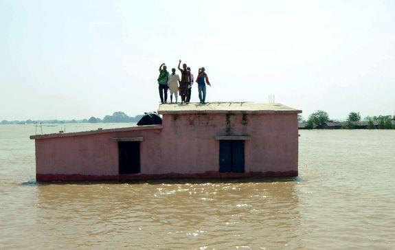 People affected by flooding in eastern Bihar state, India, wait to be rescued, Aug. 21, 2016.
