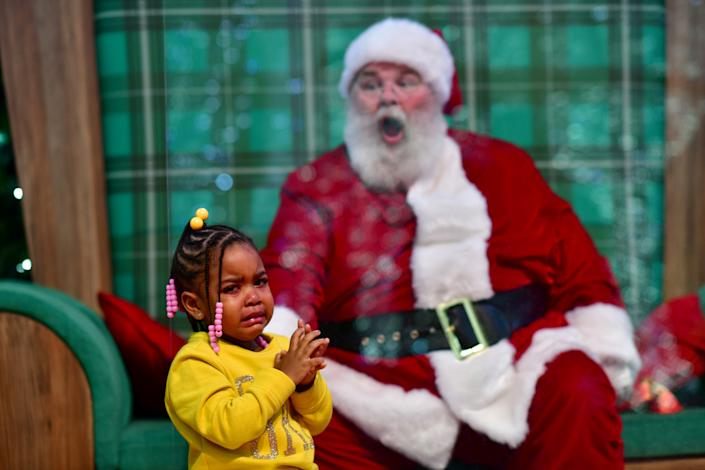Majesty Davis, 3, cries while visiting Santa Claus, who sits behind a plexiglass divider due to the coronavirus disease (COVID-19) pandemic, at the Willow Grove Park Mall in Willow Grove, Pennsylvania, U.S. November 14, 2020. REUTERS/Mark Makela     TPX IMAGES OF THE DAY