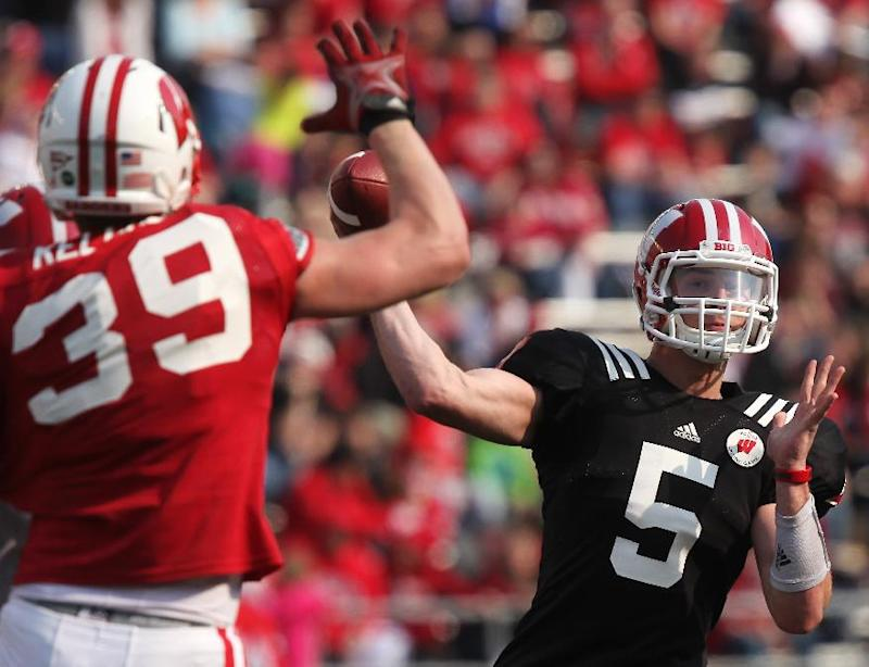Wisconsin's Tanner McEvoy (5) prepares to throw a pass as Brady Kelliher (39) defends during the second half of the NCAA college football team's spring football game Saturday, April 12, 2014, in Madison, Wis