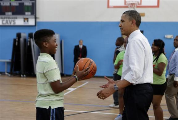 President Barack Obama talks to a boy during a visit to the Boys and Girls Club of Cleveland, Broadway section, in Cleveland, Ohio June 14, 2012.