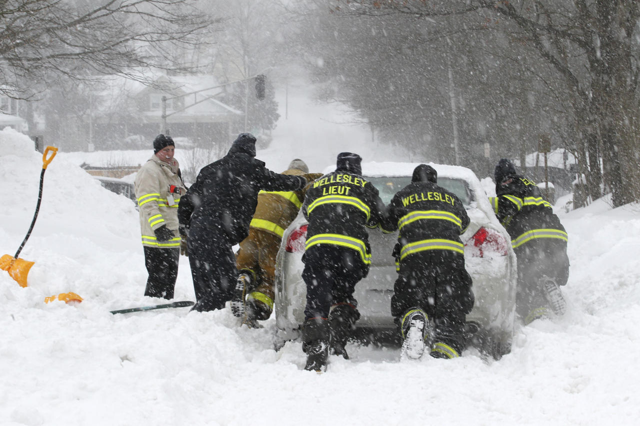 WELLESLEY, MA - FEBRUARY 9: Wellesley firefighters push out fellow firefighter Brian Beckwith after he got stuck in the blizzard approaching the station. (Photo by Bill Greene/The Boston Globe via Getty Images)