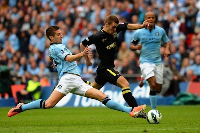 Wigan Athletic's striker Callum McManaman (R) dribbles the ball through the stretching challenge of Manchester City's defender Matija Nastasic during the English FA Cup final at Wembley Stadium in London on May 11, 2013. Wigan won 1-0