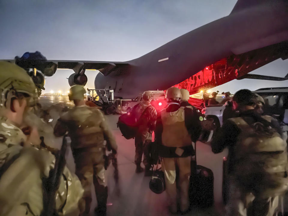 In this image provided by the U.S. Army, paratroopers assigned to the 82nd Airborne Division, and others, prepare to board a C-17 cargo plane at Hamid Karzai International Airport in Kabul, Afghanistan, Monday, Aug. 30, 2021. (Master Sgt. Alexander Burnett/U.S. Army via AP)