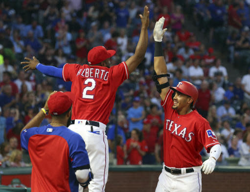 Texas Rangers' Hanser Alberto (2) leaps to high-five Ronald Guzman (67) after Guzman's home run during the fourth inning against the Kansas City Royals in a baseball game Friday, May 25, 2018, in Arlington, Texas. (AP Photo/Richard W. Rodriguez)