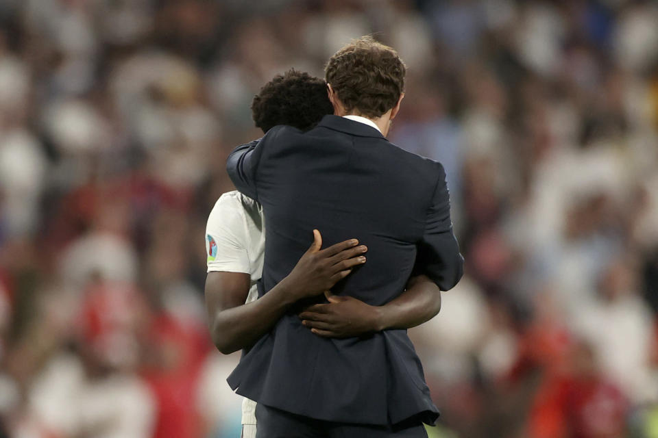 England's manager Gareth Southgate embraces Bukayo Saka after he failed to score a penalty during a penalty shootout after extra time during of the Euro 2020 soccer championship final match between England and Italy at Wembley stadium in London, Sunday, July 11, 2021. (Carl Recine/Pool Photo via AP)