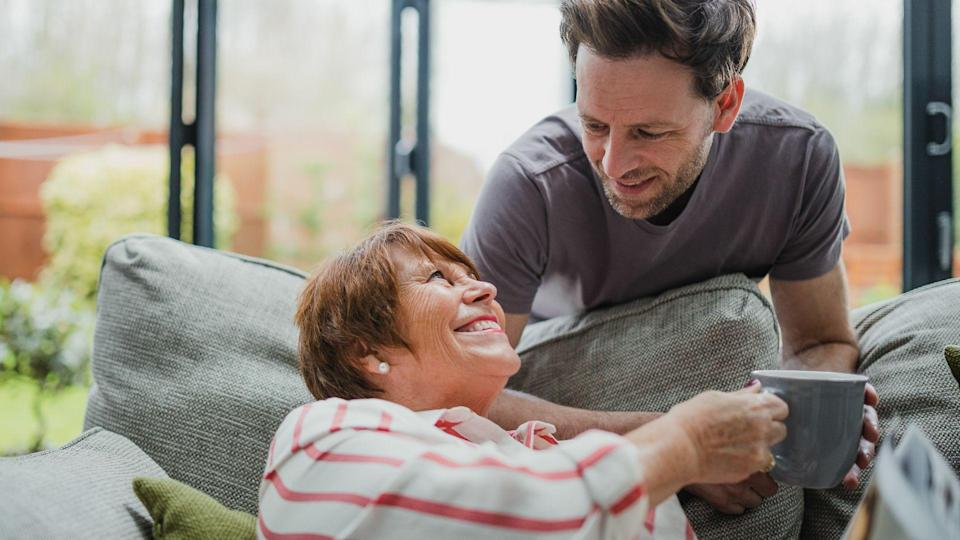 Man is leaning over the sofa to give his mother a cup of tea.