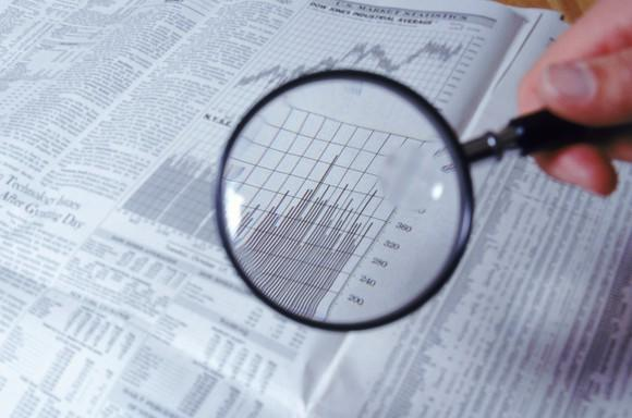 A person holding a magnifying glass over the financial section of a newspaper.
