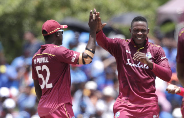 West Indies' Sheldon Cottrell, right is congratulated by Rovman Powell, left, after taking the wicket of India's Virat Kohli during the first Twenty20 international cricket match, Saturday, Aug. 3, 2019, in Lauderhill, Fla. (AP Photo/Lynne Sladky)