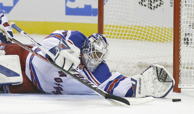 New York Rangers goalie Henrik Lundqvist, of Sweden, stops a shot on goal against the San Jose Sharks during the first period of an NHL hockey game Tuesday, Oct. 8, 2013, in San Jose, Calif. (AP Photo/Marcio Jose Sanchez)