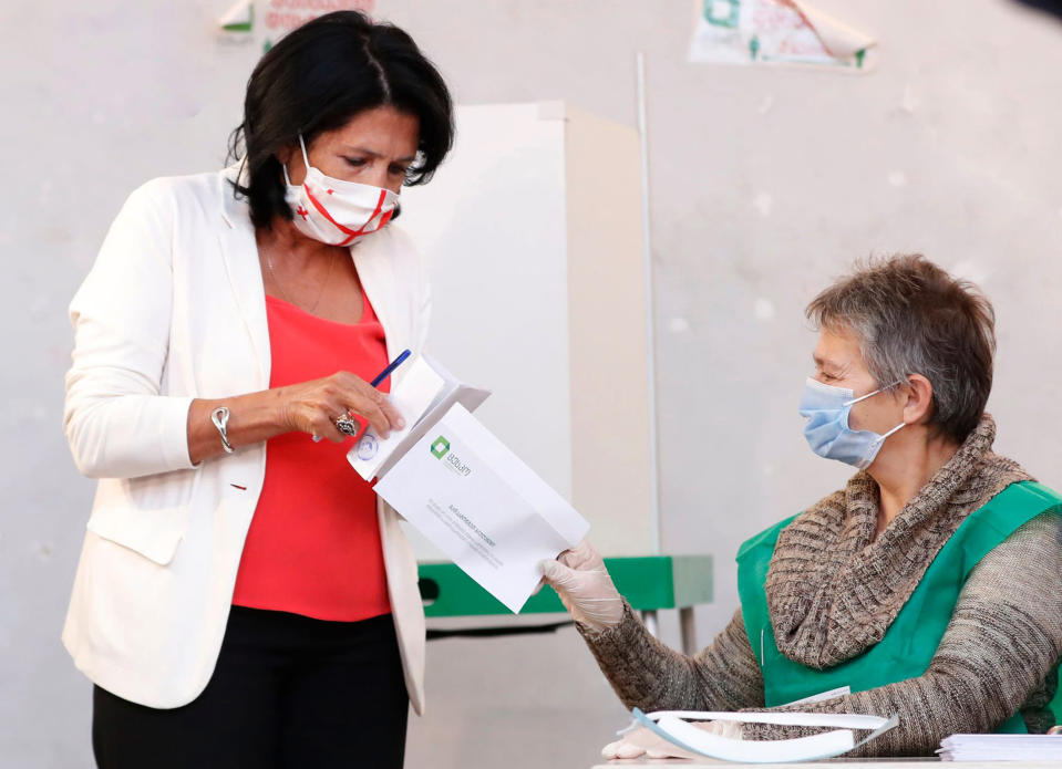 Georgia's President Salome Zurabishvili, left, wearing a face mask to help curb the spread of the coronavirus, holds her ballot preparing to vote at a polling station during the parliamentary elections in Tbilisi, Georgia, Saturday, Oct. 31, 2020. The hotly contested election between the Georgian Dream party, created by billionaire Bidzina Ivanishvili who made his fortune in Russia and has held a strong majority in parliament for eight years, and an alliance around the country's ex-president who is in self-imposed exile in Ukraine. (AP Photo/Shakh Aivazov)