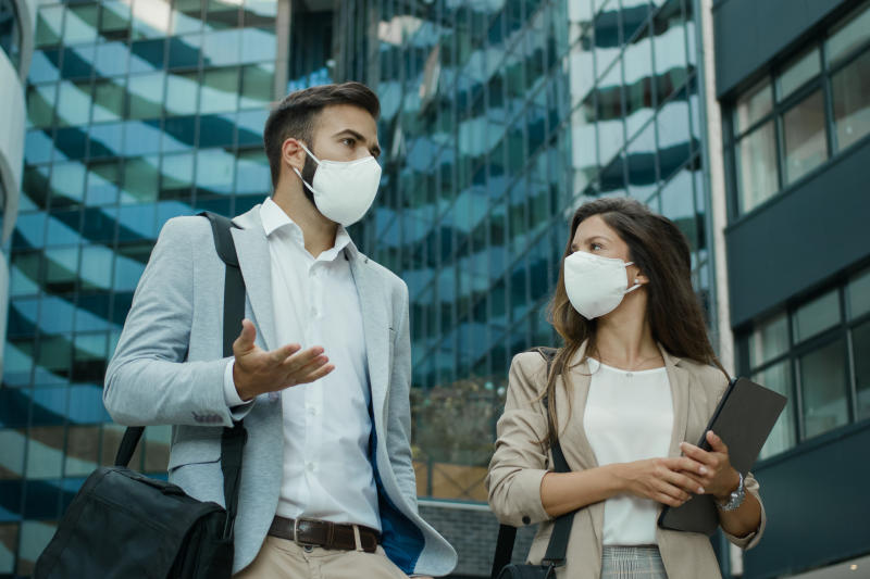 Two business people wearing protective face masks and talking to each outdoors