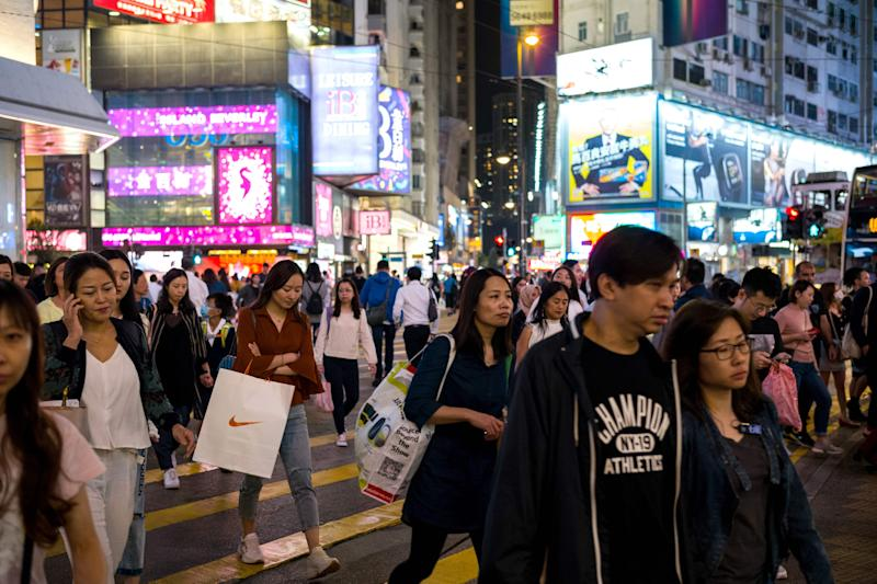 Pedestrians cross a road in the popular shopping district of Causeway Bay in Hong Kong on October 30, 2019, a day before the citys third-quarter gross domestic product (GDP) figures are released. (Photo by Anthony WALLACE / AFP) (Photo by ANTHONY WALLACE/AFP via Getty Images)