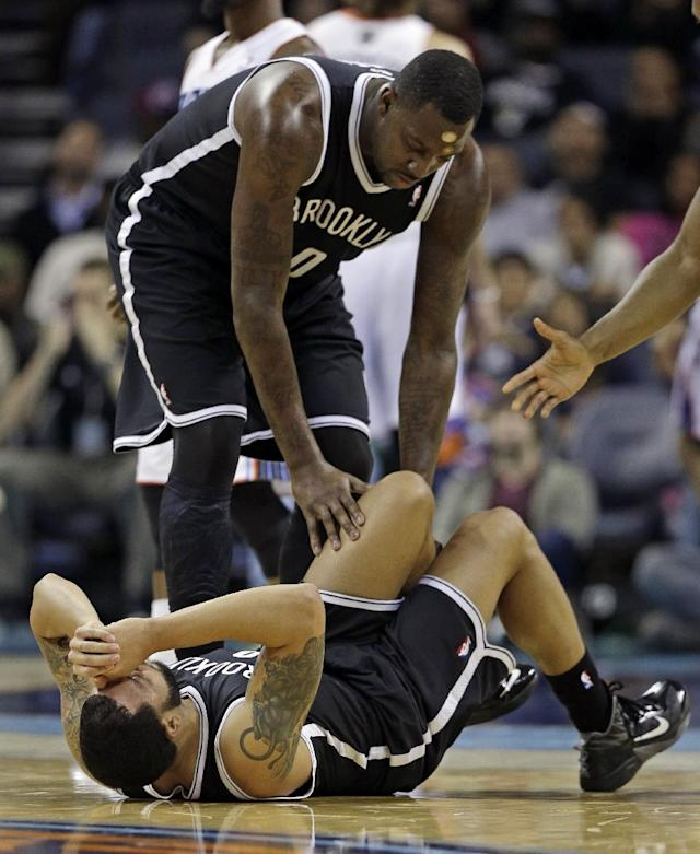 Brooklyn Nets' Deron Williams, bottom, is helped by teammate Andray Blatche after being injured during the first half of an NBA basketball game against the Charlotte Bobcats in Charlotte, N.C., Wednesday, Nov. 20, 2013. The Nets announced Williams has a sprained ankle and will not return to Wednesday's game. (AP Photo/Chuck Burton)