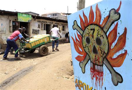Men push their handcart past a danger sign at the sprawling Kibera slums in Nairobi