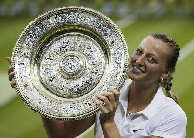 Petra Kvitova of Czech Republic holds the trophy as she poses for photographs after winning the women's singles final defeating Eugenie Bouchard of Canada at the All England Lawn Tennis Championships in Wimbledon, London, Saturday, July 5, 2014. (AP Photo/Pavel Golovkin)