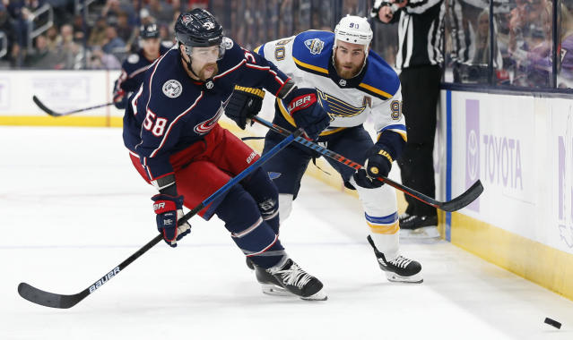 Columbus Blue Jackets' David Savard, left, and St. Louis Blues' Ryan O'Reilly chase the puck during the first period of an NHL hockey game Friday, Nov. 15, 2019, in Columbus, Ohio. (AP Photo/Jay LaPrete)