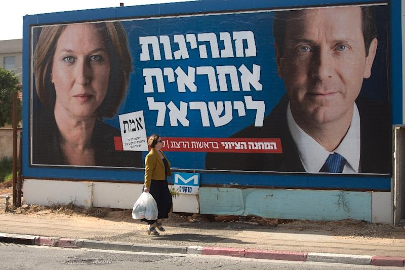 An Israeli woman passes by a campaign poster showing Israeli MP Tzipi Livni (L) and Isaac Herzog co- leaders of the Zionist Union party on March 8, 2015 in the Israeli city of Tel Aviv (AFP Photo/Menahem Kahana)