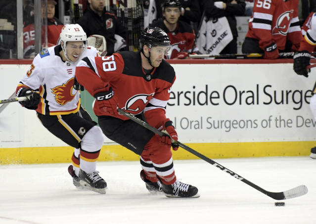 New Jersey Devils center Kevin Rooney (58) skates with the puck as he is pursued by Calgary Flames left wing Johnny Gaudreau (13) during the second period of an NHL hockey game Wednesday, Feb. 27, 2019, in Newark, N.J. (AP Photo/Bill Kostroun)