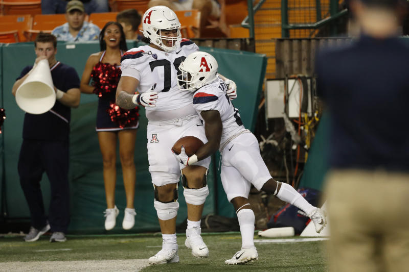 After scoring a second half touchdown against Hawaii, Arizona running back J.J. Taylor (21) celebrates with offensive lineman Donovan Laie (78) during an NCAA college football game, Saturday, Aug. 24, 2019, in Honolulu. (AP Photo/Marco Garcia)