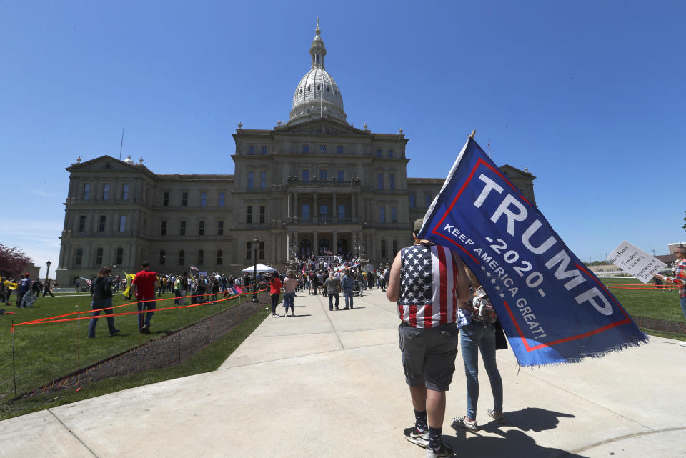 Protesters carry a Trump 2020 flag at the State Capitol during a rally in Lansing, Mich., Wednesday, May 20, 2020. Barbers and hair stylists are protesting the state's stay-at-home orders, a defiant demonstration that reflects how salons have become a symbol for small businesses that are eager to reopen two months after the COVID-19 pandemic began. (AP Photo/Paul Sancya)