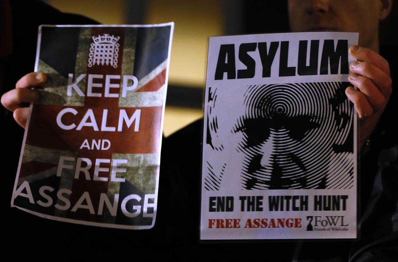 Supporters hold banners as they wait for Julian Assange, founder of WikiLeaks to speak to the media and members of the public from a balcony at the Ecuadorian Embassy in London, Thursday, Dec. 20, 2012. Assange who faces extradition to Sweden over sexual assault, claims which he denies, took refuge in the embassy in June. (AP Photo/Kirsty Wigglesworth)